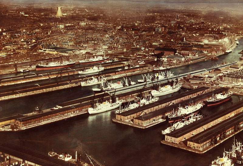 A superb colour picture showing the Prince's and Queen's Docks - the main user of the Centre Basin of the Princes Dock was the Glasgow-based Donaldson Line and three of their ships can be seen in the basin.<br /> <br /> Also prominent in this picture is the huge cooling tower of Pinkston Power Station in north of the city. It was constructed by Glasgow Corporation at the start of the 20th Century to supply power for their new fleet of electric tramcars. It stood beside the Glasgow Branch of the Forth & Clyde Canal from which it drew cooling water.