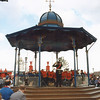 "The Overtoun Bandstand being used for the its intended purpose.<br /> <br /> It was gifted to the Royal Burgh of Rutherglen in 1914 by local firm J & J White. James White and his wife had a family of 6 girls and one boy at their home, Hayfield, near Rutherglen but later he had a large mansion built at Overtoun in the Kilpatrick Hill's above this wife's home town of Dumbarton. After his death his son, John Campbell White assumed control of the business. He was active in many aspects of public life including politics. As a result of his involvement in the Liberal party he received a peerage and assumed the title Lord Overtoun.  <br /> <br /> White's chromate manufacturing works in Rutherglen (known as Shawfield Chemical Works) were the largest in the UK employing 900 at its peak. However, the works were something of a mixed blessing. Alhough it provided employment, the workers were exposed to horrible chemical contamination that ate away at the bones in their faces and fingers producing terrible and painful disfigurements. Their clothes were covered in harmful yellow dust and they were known locally as 'White's Canaries' Also the ash wastes from the process were dumped and buried at various sites around the town  from which the poisons leeched into the soil and the Clyde - and probably the food chain. Lord Overtoun donated Overtoun Park to Ruglonians and it was set out for recreational sports, principally football but the ash parks were created with waste material from the chromate works! Overtoun Park opened a century ago on 25th May 1908 but Lord Overtoun did not see it as he died a few weeks earlier on 15th February. Perhaps the Overtoun Bandstand should be a memorial to all those who suffered in the cause of the the bichromates of potassium and sodium.  <br /> <br /> More information on James White can be studied at:<br /> <br /> <a href=""http://gdl.cdlr.strath.ac.uk/mlemen/mlemen098.htm"">http://gdl.cdlr.strath.ac.uk/mlemen/mlemen098.htm</a><br /> <br /> See also the Overtoun House website:<br /> <br /> <a href=""http://www.overtounhouse.com/index.php"">http://www.overtounhouse.com/index.php</a><br /> <br /> The Overtoun Bandstand can be seen in Rutherglen park"