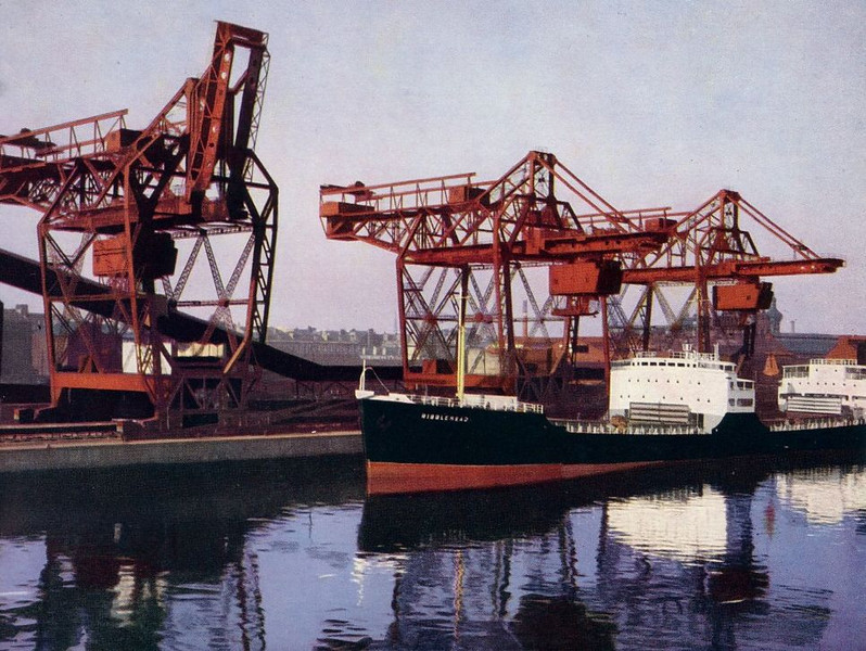 """A view of the three ore unloaders at General Terminus Quay with the bulk carrier Ribblehead, built by Lithgows of Port Glasgow alongside. Details at:<br /> <br />  <a href=""""http://www.clydesite.co.uk/clydebuilt/viewship.asp?id=18436"""">http://www.clydesite.co.uk/clydebuilt/viewship.asp?id=18436</a><br /> <br /> The aerial view of the Terminus at the SCRAN web link gives a good impression of the whole complex including the railway which approached from the south on a line parallel to Seaward Street.<br /> <br />  <a href=""""http://www.scran.ac.uk/database/record.php?usi=000-000-117-817-C&PHPSESSID=t86f3its70n71acedircv3usf1&scache=52j2t21vou&searchdb=scran"""">http://www.scran.ac.uk/database/record.php?usi=000-000-117-817-C&PHPSESSID=t86f3its70n71acedircv3usf1&scache=52j2t21vou&searchdb=scran</a><br /> <br /> Also shown in the link photo is the terminal of the elevating deck vehicle ferry to Finnieston at Elliot Street and (across the Road) the works of the Clyde Galvanising Company. At the top, left of the picture is Springfield Quay and the Riverside Mills. <br /> <br /> Extra deepening of the river upstream of Queen's Dock allowed ships drawing 30 feet of water to berth at the Terminus and a peak of 2.73 million tons of iron ore was discharged in 1961. However, even as the facility opened in 1957 it was becoming clear that many of the future ore carrying ships would be so large they would not be able to come up the River Clyde."""