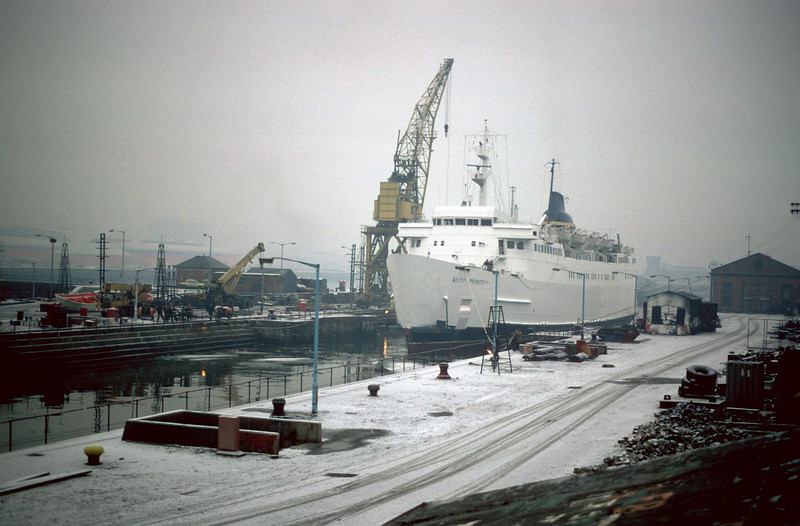 On a cold foggy and snowy Clyde day in 1984 Sealink's Stranraer - Larne ferry Ailsa Princess is seen stemming into the No 3 drydock from the Princes Dock canting basin. The large yellow travelling crane was one of two that worked the Govan Graving Docks. In common with the three drydocks the cranes were listed as being of importance in industrial heritage and architectural terms. Unfortunately, this classification did not prevent the the structures from being illegally destroyed when ClydeDock abandonned the historic dockyard in the mid 1980s. It has been suggested that this action was taken to make the site more attractive to property developers. However, over twenty years later the historic dockyard remains derelict and wantonly vandalised. The chance to create a world class maritime heritage centre to commemorate the River Clyde's enormous and unequalled contribution to world shipbuilding and engineering was actively discouraged and prevented by government and development agencies. Only in the UK could important industrial and social heritage be dismissed in favour of characterless and unremarkable property development and, so-called, urban renewal.