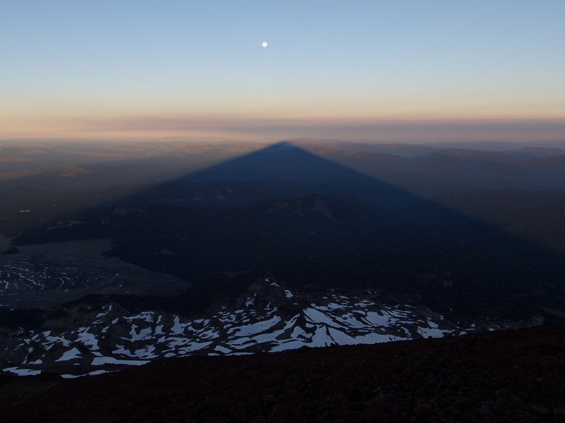 This is the shadow of South Sister at sunrise, taken from the top of the mountain, looking to the west as the full moon is on it's way down; the shadow of the mountain shrinks as the sun climbs.  It's a spectacular sight to watch
