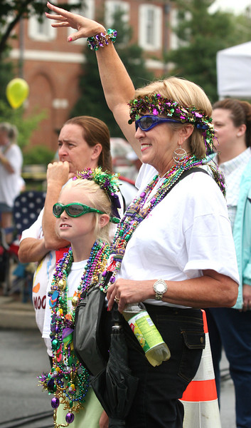Wanda Lifford and her granddaughter Mikaela, 8, reach for mardi gras beads at the main stage. E9071307 Photo by Erica Yoon