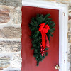 Bright red welcoming door with Christmas wreath.