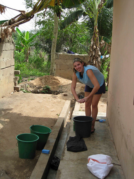 "Chelsy in the ""laundry room"". Everything is hand washed. <br /> <br /> The pile of sand to her left has a 3-4 ft pit, that's the drain for the ""washer"" as well as the part time garbage disposal- The remaining garbage is left on the gorund where the goats, chickens and dogs dine."