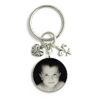 "Gift_K_02, $50<br /> This darling keychain features a 1"" round photo that is accented perfectly with heart and fleur de lis charms.  Your photo is reproduced and sealed making the pendant waterproof, fadeproof & scratch resistant.  Sterling Silver."