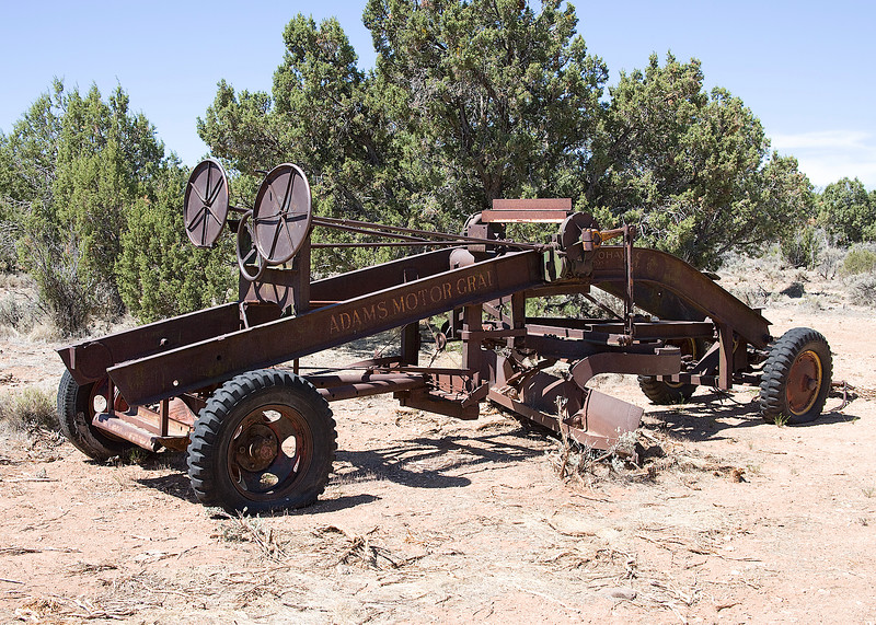 Must date around the late 20's?  It's an early Adams Motor Grader, Pretty cool.  I think it had an engine on it at one time?