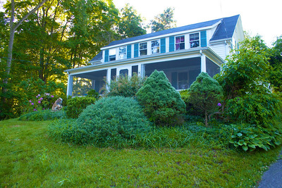 The screened-in front porch is 30 x 8 feet with a hanging sofa swing. Rhododendrons grow on either side of the porch