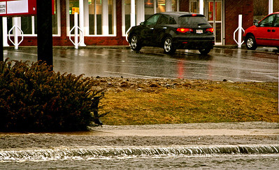 Water over flowing across the side walk and into the street.