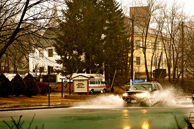 Cars plow through the flooded street.