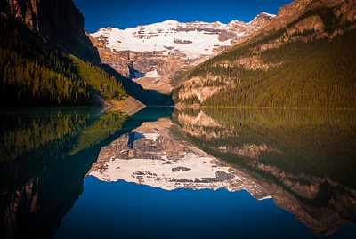 Perfect peaks reflexion on calm water of Lake Louise in the morning, Banff National Park, Alberta, Canada