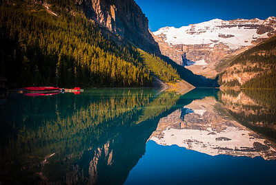 Turquoise water of Lake Louise with contrasting red canoes and snow capped peaks, Alberta, Canada