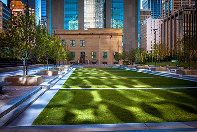 Building light reflection on grass of downtown Calgary, Alberta, Canada