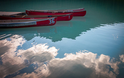 Red canoe line and cloud reflection on turquoise water of Lake Louise, Banff National Park, Alberta, Canada.