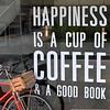 A bicycle and a slogan in a cafe at the Seenspace shopping centre in Hua Hin, Thailand in August 2017.  Happiness is a cup of coffee and a good book
