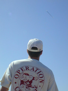 Catapult: Glider in sky with Shane and his Operation Catapult shirt and MIT hockey hat.