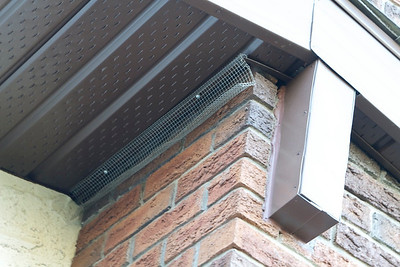 Here's another view of chimney area.  Up near the top-left of the beam cap the soffitt fit is worse than it was before the tin was replaced. Brown screws would have been a good idea; available at Home Depot, Rona, and every other home improvement outlet.