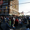 Crowds gather to watch the parade under a clear blue sky and sunshine.