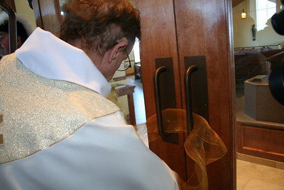 Fr. Bob unties the ribbon that seals the doors to the new church.