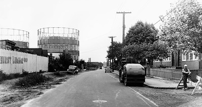 57th Avenue at 73rd Street, Looking East.  Utilities were either being installed or repaired along 57th Avenue when this photo was taken. We see a worker on 73rd Street resting off to the right. At left, we see the fence of the Elmhurst Lumber Corp. and some 1-story homes. The most noticeable part of the streetscape is the sight of the Elmhurst Gas Tanks off in the distance.  But the gas tanks are now gone, soon to be replaced by Elmhurst Park.