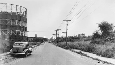 57th Avenue at 74th Street, Looking East.  Once again, the thing that draws one's attention is the Elmhurst gas tank on the left. The Brooklyn Union Gas plant can be seen in the background near the tanks. Alone 1930s-era car is parked along the road.  The most prominent structures on the right are telephone poles. The Long Island Expressway has not yet been constructed, and the landscape where it now stands was nothing but a field of trees and weeds in 1940.