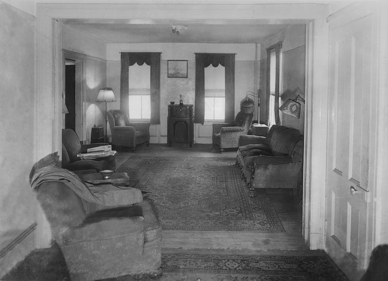 Residential living room  This is the interior of a home along 57th Avenue. Each sitting area had a floor lamp to foster reading. As this was before the advent of television, DVD players and VCRs, the entertainmnet center consisted of just a radio.