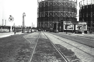 Grand Avenue, looking east from 74th Street.  The view has changed dramatically since this photo was taken. Most noticeably, the Brooklyn Union Gas Tanks are gone. They were dismantled in 1996. There are no more trolley tracks in the roadbed, and the Belgian blocked streets have all be asphalted over. There still is a gas station on the far left, a body shop further down the street on the left, and factory buildings on the far right. St. Adalbert Roman Catholic Church can be seen under the Texaco sign in the distance.