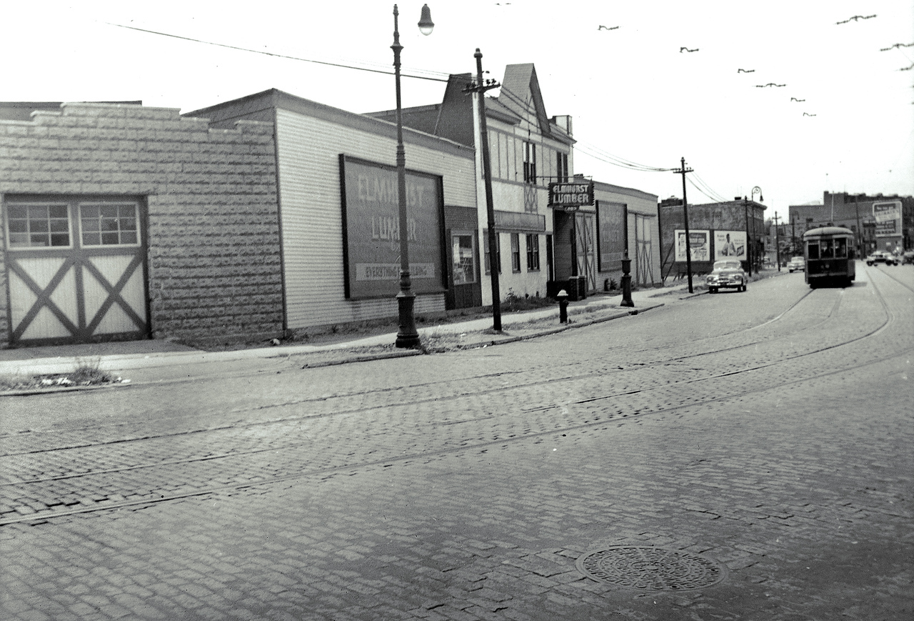The Elmhurst Lumber Corporation owned a large parcel of land on the south side of Grand Avenue (and the north side of 57th Avenue) between 72nd and 74th Streets. Today, everything in this picture has been replaced by