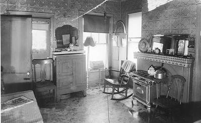 Office converted into kitchen.  This kitchen was once used as an office. The defunct fireplace now has a stove/oven in front of it. None of the chairs match and were probably collected from residential trash. Note the pressed tin on the walls.