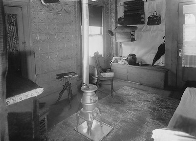 Store converted into living quarters  The shuttered store seen in the previous exterior photo was being used as living quarters. It was common to find these types of conversions during the Great Depression. The centerpiece of the room is a coal-burning heater.
