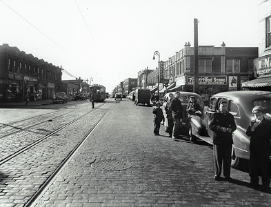 Grand Avenue east of 71st Street, looking west.  Teens wait for the trolley in front of Nash's Pharmacy while a policeman directs traffic at the intersection. We see Tom's Food Store, Fiederer Bakery and Walter's Delicatessen on the right. On the left is Janison's Jewelry Store, a candy store, Burton's Plumbing Supply, Leo's Shoes, a store selling Venetian Blinds and Sontag's Paint and Hardware Store. Though the stores have changed, the streetscape looks very much the same today.