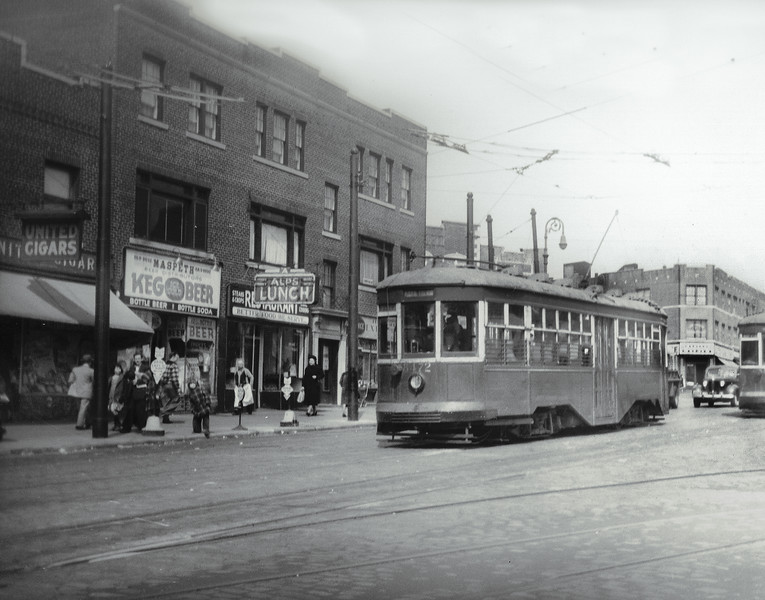 Here we see Grand Avenue from 68th Street, looking northeast.  The building to the extreme right is where Joey's Pizza is today at 69th Street and Grand Avenue. Behind the trolley is a set of buildings at Borden Avenue and 69th Street, one of which contained Maspeth Federal Savings, which had opened in 1947.  The rest of the buildings seen along Grand Avenue were demolished in the  1950s to make way for the Long Island Expressway. From left to right were  United Cigars, Maspeth Keg O Beer, Alps Lunch and an exterminator's office.  The trolley shown was replaced by the Q58 bus route.