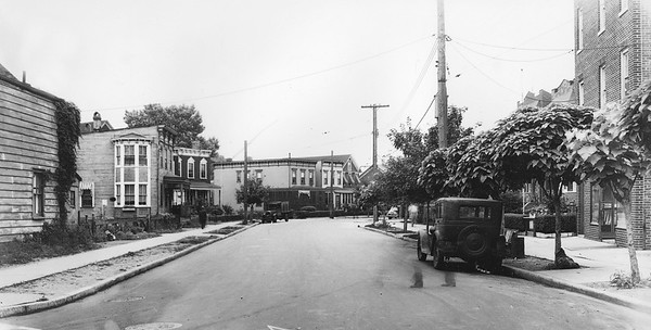 Mazeau Street, looking south from 57th Avenue.   Much of Mazeau Street remains the same today, with some of the homes here dating back to the 19th century. The house on the corner at left has been replaced by a laundromat. The house with the peaked roof in the distance and its neighbor became a controversial construction site in recent years. In 1940, the 3-story mixed-use building on the right had Nick Scarane's Tailor Shop as a tenant on the ground floor.