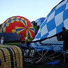 Volunteers hold Propane Exceptional Energy Balloon's mouth open to get cool air in their and inflate balloon.