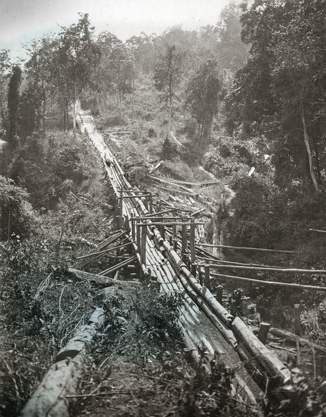 """The 1st bridge over the H Kan at the foot of the 1/2 mile of steep descent. Logs cross the bridge at over 60 miles an hour. Note the trail of smoke  and dust behind the log descending."""