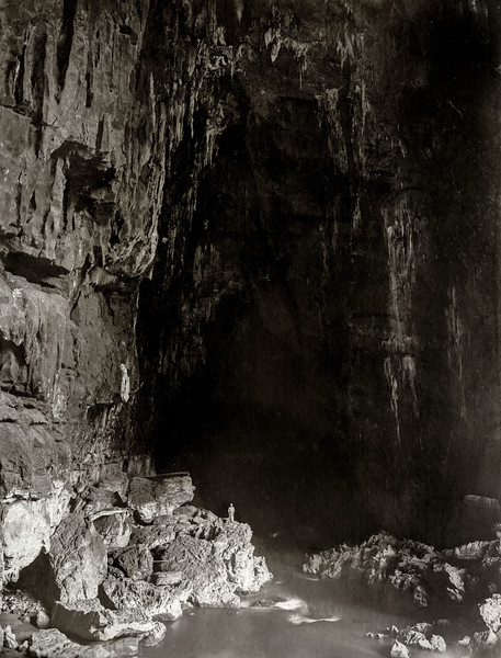 """Further in the cave (note man on rocks.)"""