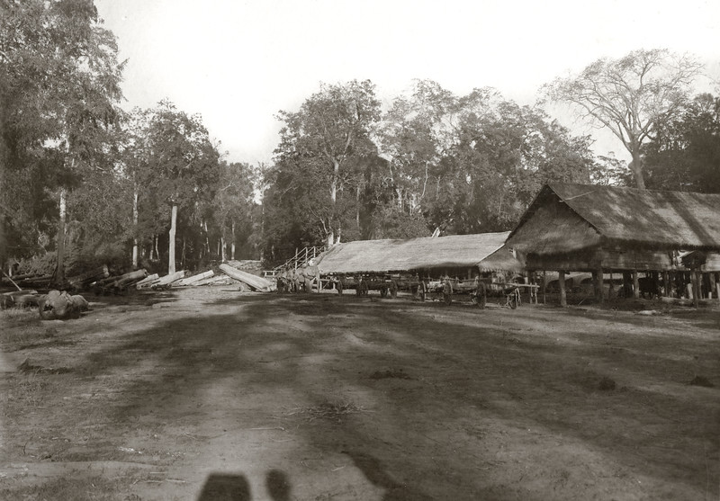 """Cart shed and barracks for men. Note big log being carted by two elephants."""