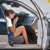 Woman prays in police car.
