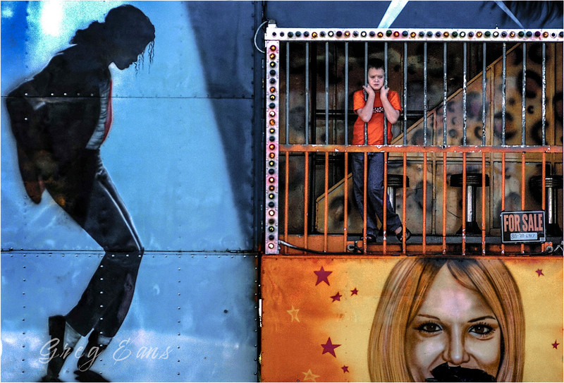 Third-grader Adam Joyner peeks from behind the bars of the Rock and Roll Fun House while visiting the Pitt County fair with his classmates on a field trip.<br /> *This photo was feataured in MSNBC's The Week in Pictures.