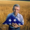 Portrait of Veteran Bob Franke with American flag in wheat field. North Carolina.