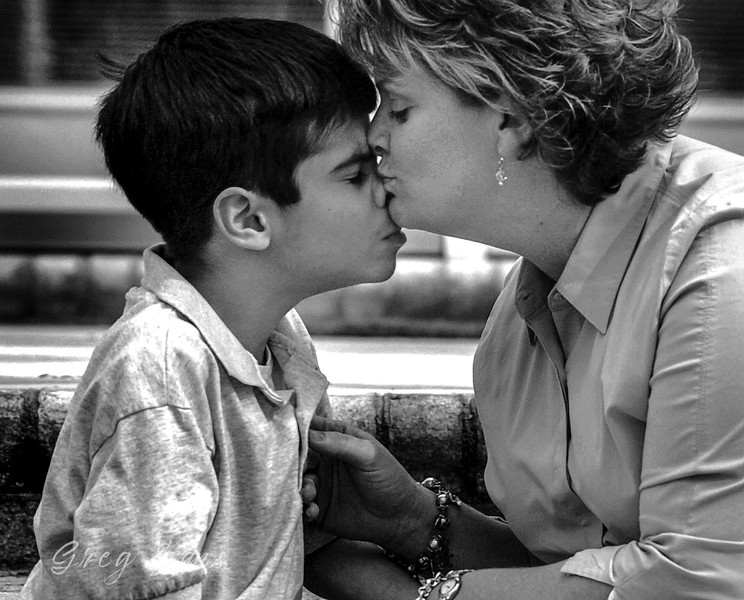Jacob Kowalski, who suffers from autism,  gets a kiss on the nose from his school teacher Cathy Tripp during a meeting of Jacob's Circle of Friends at his home.