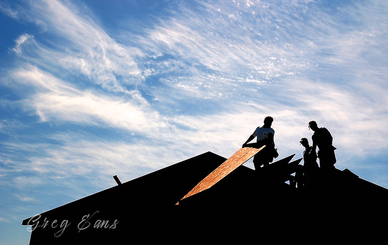 Habitat for Humanity volunteers work on the roof of a home they are building.