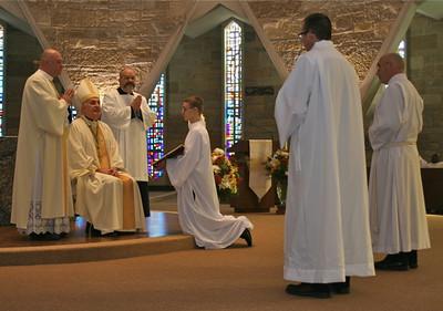 SCJ candidate Justin Kemke, kneeling before the bishop, served as crucifer