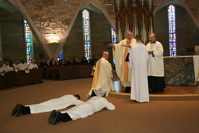 Greg and Clint lay prostrate before the bishop