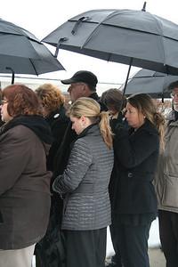 Huddled under the umbrellas; a light mist damped the day but not spirits
