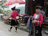 There are Yao  minority people here as well, as are these two women.  They have thin faces and long shiny black hair.  The black and red attire is typical.