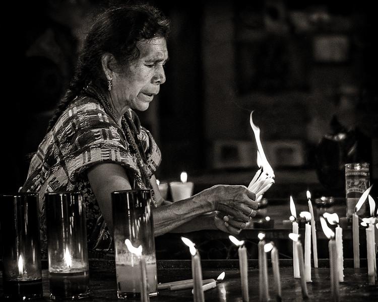 Worshipper burning candles, Temple of St. Simon (Maximón), San Andrés de Itzapa, Guatemala
