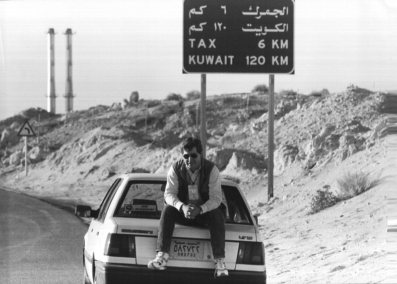 Kahfji,Saudi Arabia- On the Saudi-Kuwati Border, Todd Buchanan sits on the trunk of the rental car used to get around the Saudi front lines in the lead up to the Gulf war in 1991. Photo by Charlie Borst  Dec. 1991