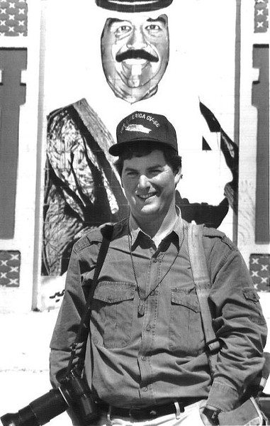 Kuwait City,Kuwait- A Portrait of Sadaam Hussein erected outside this city serves as a backdrop behind Todd Buchanan after the liberation of the city during the Gulf war in 1991. Photo by Christopher Morris  Feb. 1991