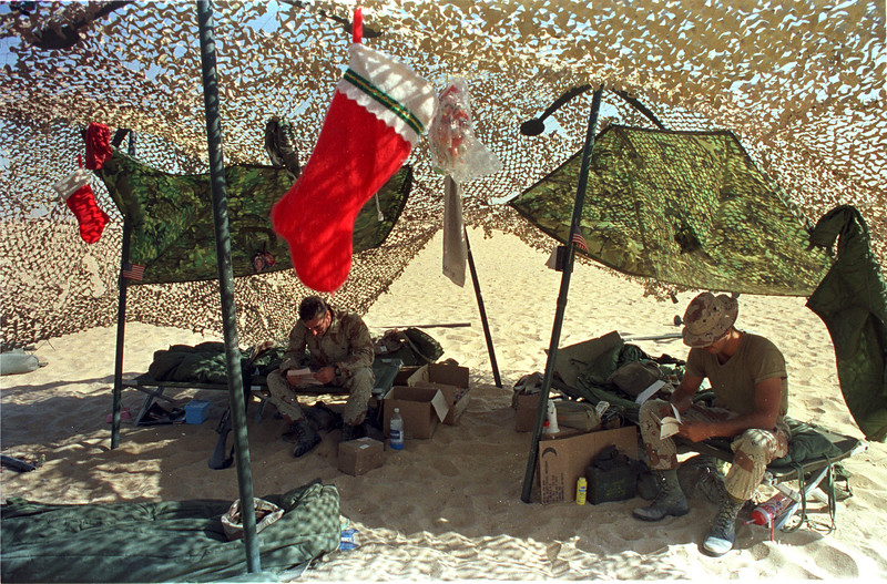 U.S. Marines read letters from home under the camoflage nets in the desert near Christmas time. Holidays, preperation, war, christmas decorations, stockings Photo by Todd Buchanan