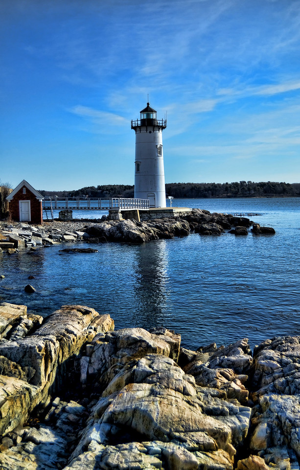 Lighthouse with rocky shore in foreground, Portsmouth, New Hampshire.